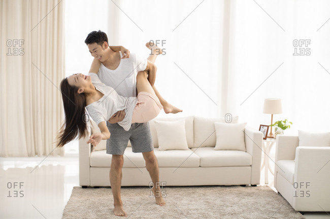 Young Chinese couple having fun in living room