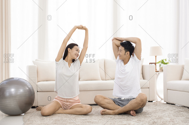 Young Chinese couple exercising in living room