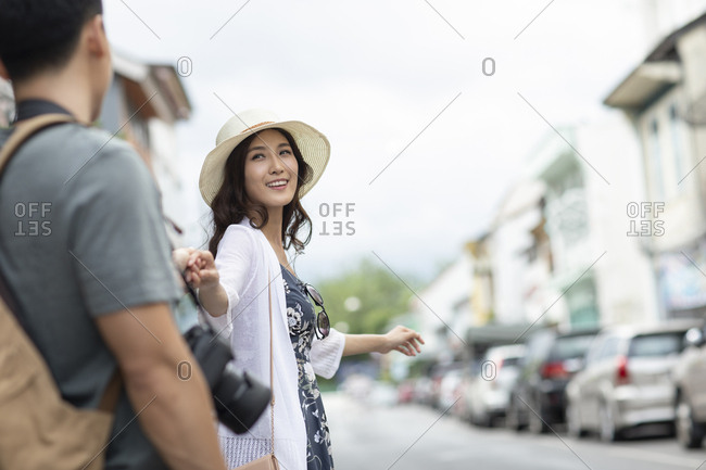 Happy young Chinese couple holding hands on street