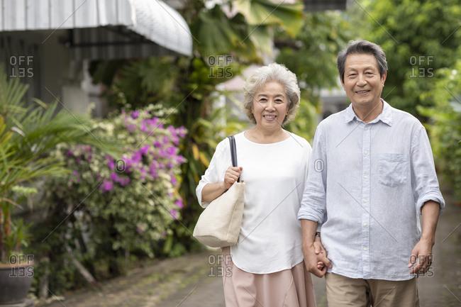 Happy senior Chinese couple holding hands