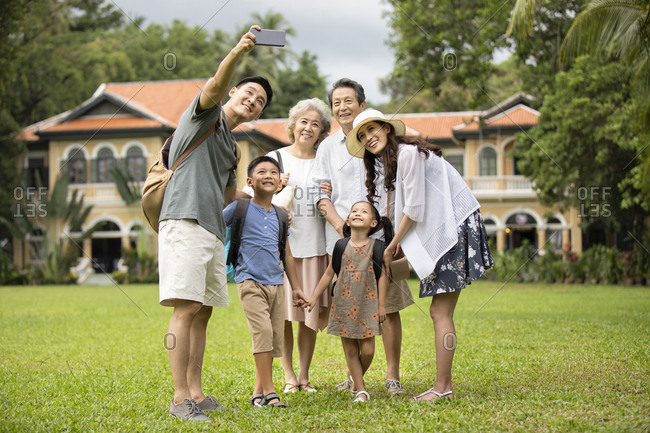 Happy Chinese family taking selfie on meadow