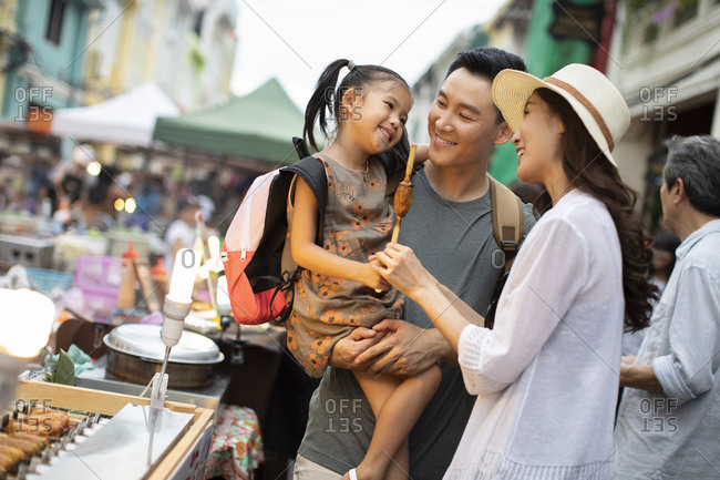 Happy young Chinese family eating snack in market