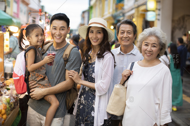 Happy Chinese family relaxing in street market
