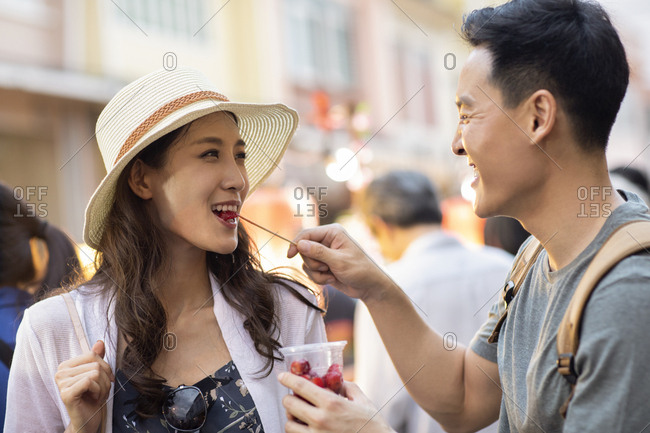 Happy young Chinese couple eating street food in street market