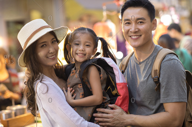 Happy young Chinese family relaxing in street market