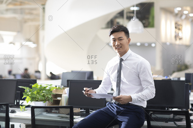Young Chinese businessman holding file in office