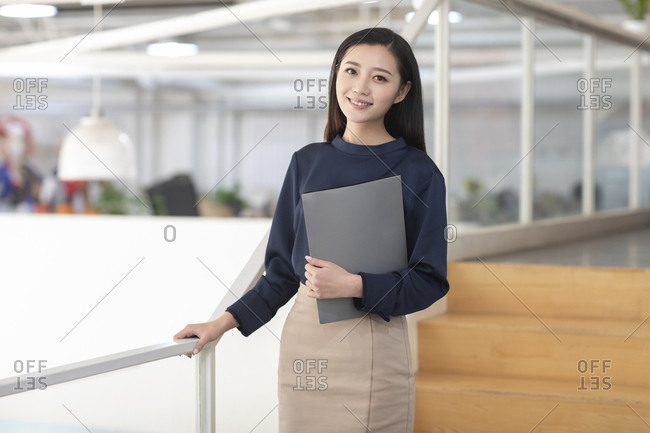Young Chinese businesswoman holding file in office