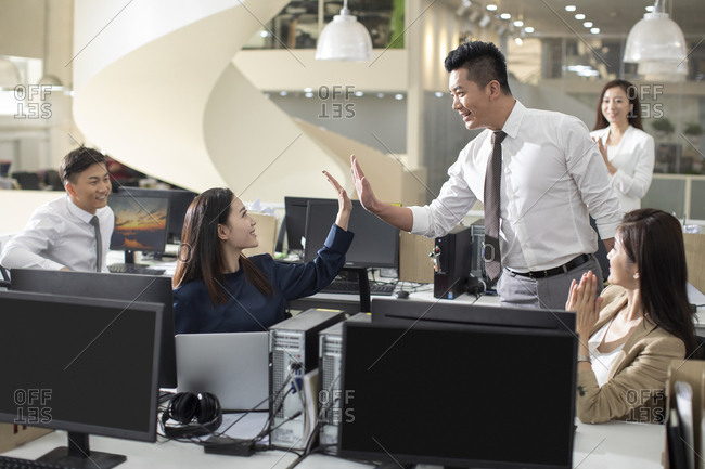 Chinese business people giving high five in office