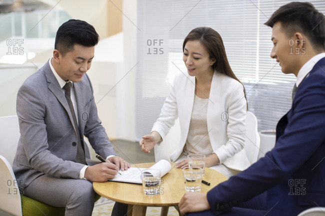 Chinese business people signing contract in office