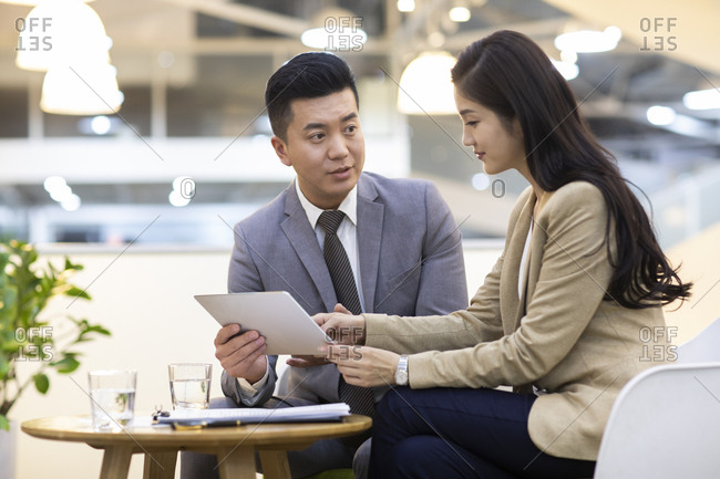 Chinese business people using digital tablet in office