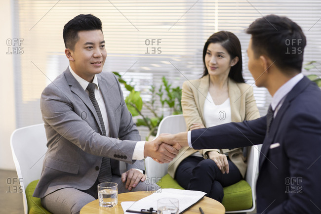 Chinese business people shaking hands in office