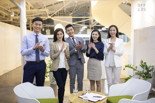 Chinese business people clapping hands in office
