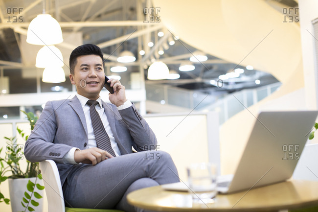 Chinese businessman using smartphone in office