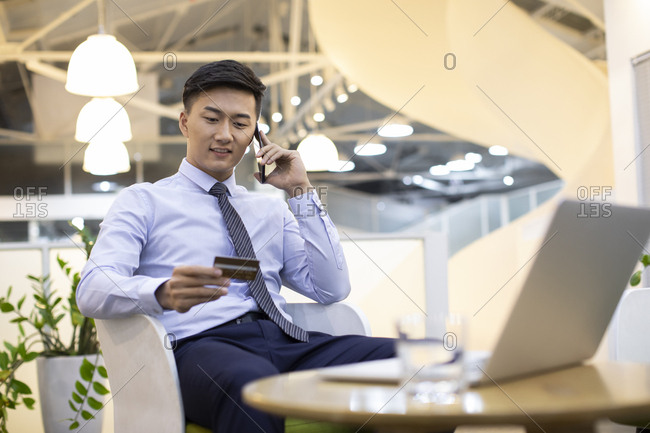 Young Chinese businessman shopping online in office