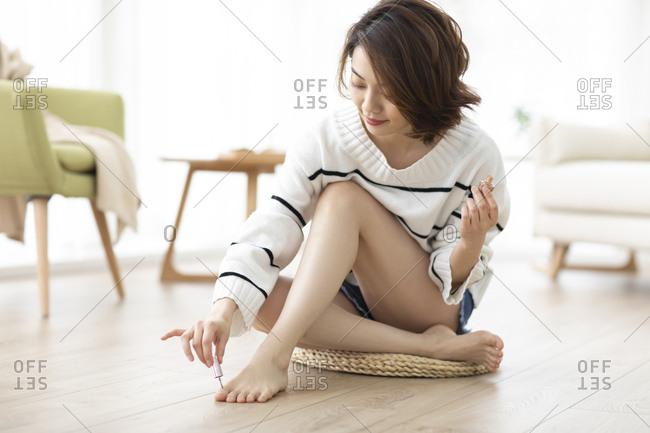 Happy young Chinese woman applying nail polish at home
