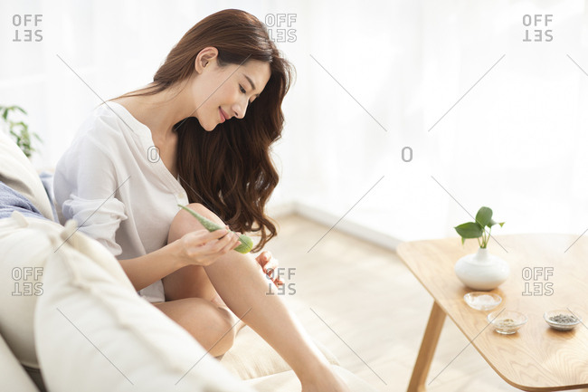 Young Chinese woman with natural aloe vera at home