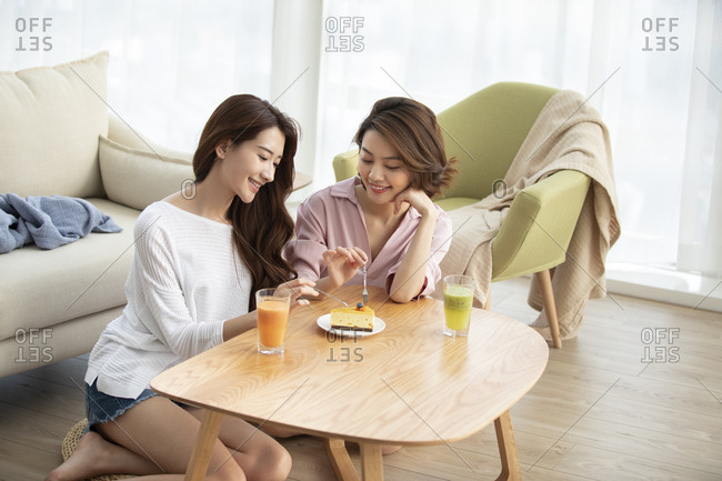Young Chinese friends having afternoon tea at home