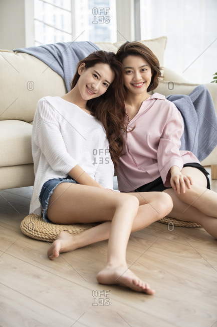 Young Chinese friends relaxing in living room
