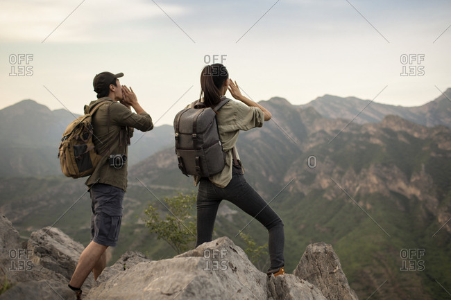 Young Chinese couple shouting on mountain peak
