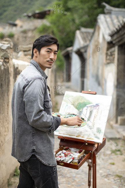 Young Chinese artist painting outdoors