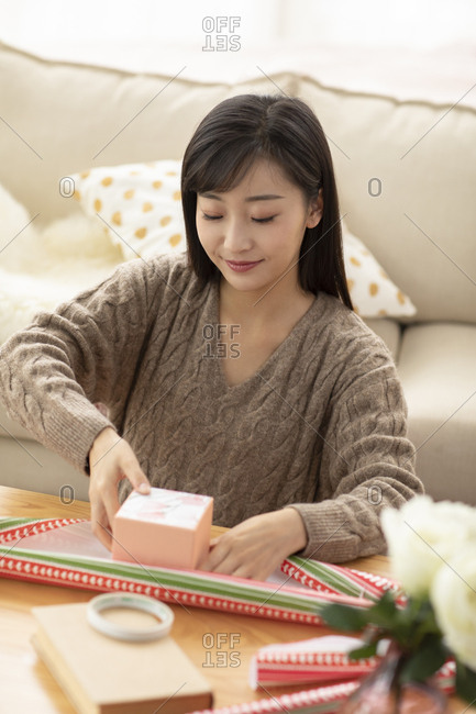 Young Chinese woman wrapping gift in living room