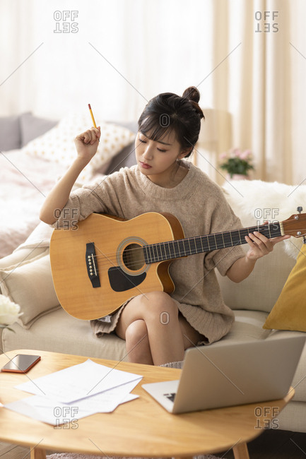Young Chinese woman playing guitar at home