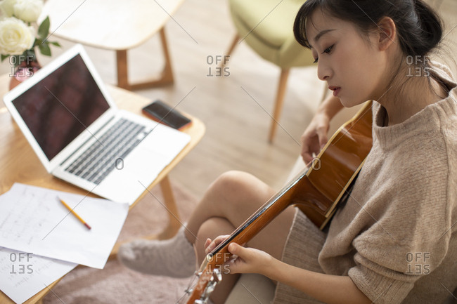 Young Chinese woman writing music at home