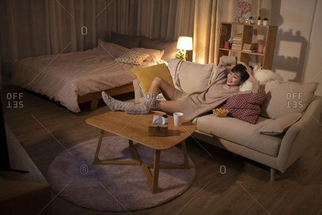 Young Chinese woman watching TV on sofa