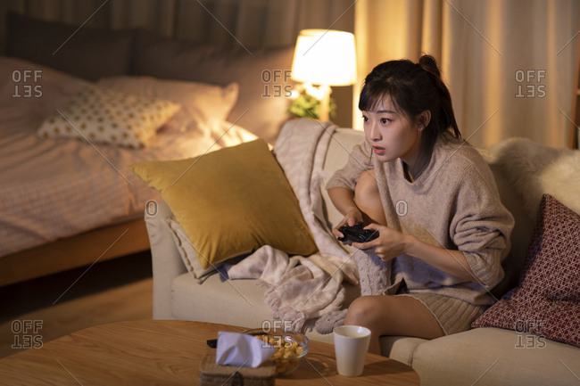 Young Chinese woman playing video game on sofa