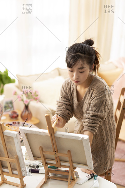 Young Chinese woman painting at home