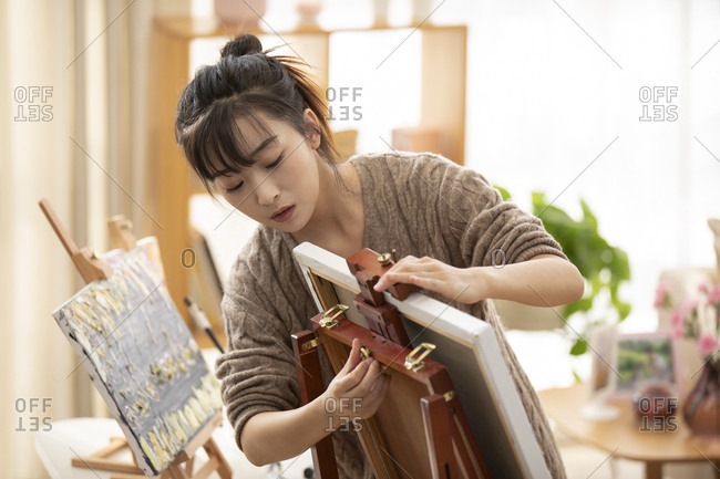 Young Chinese woman preparing for painting at home