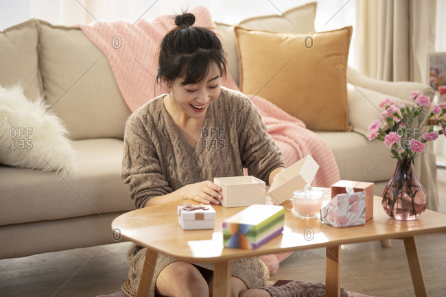 Young Chinese woman opening gift box at home