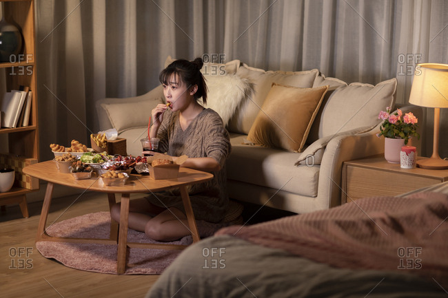 Young Chinese woman eating take-out food at night