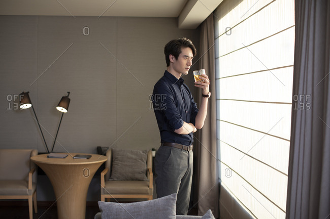 Young Chinese businessman drinking alcohol in front of window