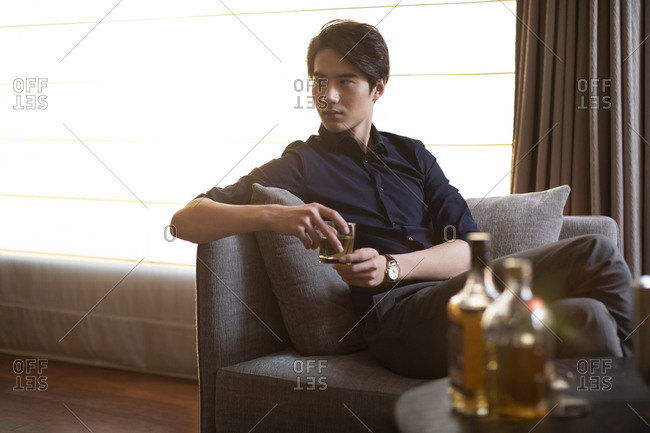 Young Chinese businessman drinking alcohol in hotel room