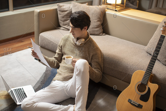Young Chinese man writing music at home