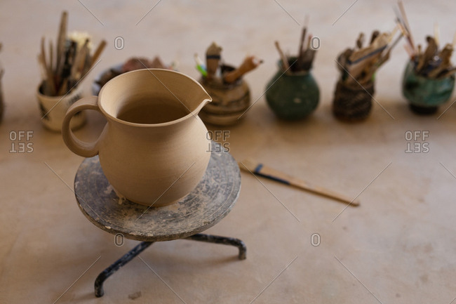 Elevated view of a clay jug on a banding wheel sitting on a work top at a pottery studio, with pots and tools in the background