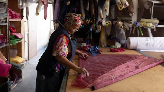 Side view of a middle aged mixed race woman standing at a table working with fabric at a hat factory.