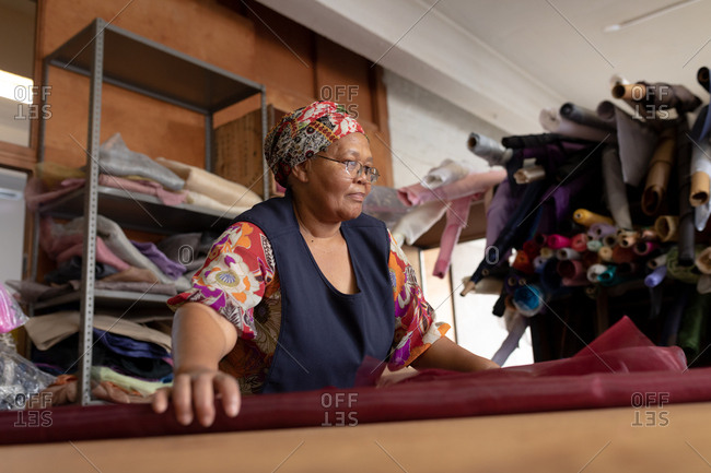 Front view close up of a middle aged mixed race woman standing at a table working with fabric at a hat factory.