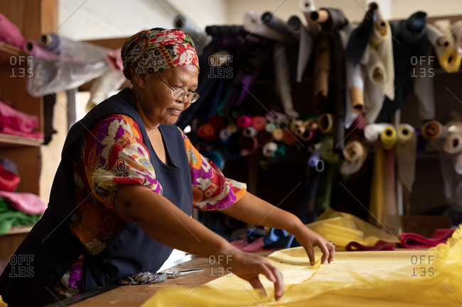 Side view close up of a middle aged mixed race woman standing at a table working with yellow fabric at a hat factory.