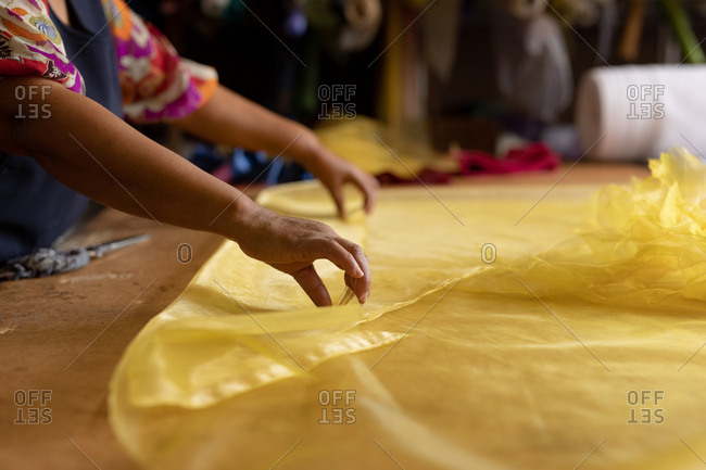 Side view mid section of a middle aged mixed race woman standing at a table working with yellow fabric at a hat factory
