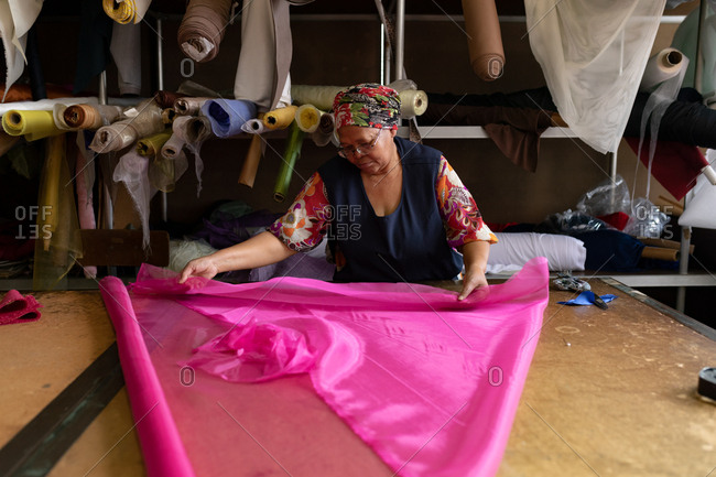 Front view of a middle aged mixed race woman standing at a table folding and measuring out lengths of pink fabric at a hat factory.