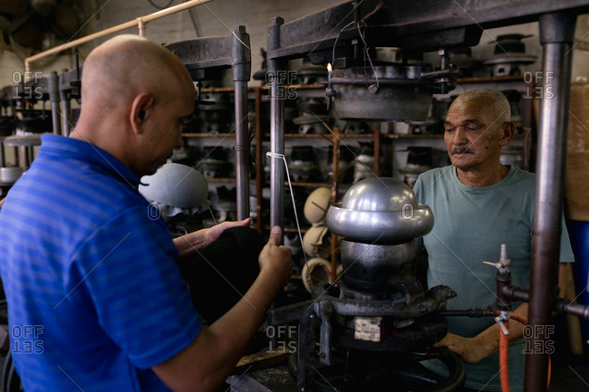 Side view close up of a senior and a middle aged mixed race man working together at a machine in the workshop at a hat factory