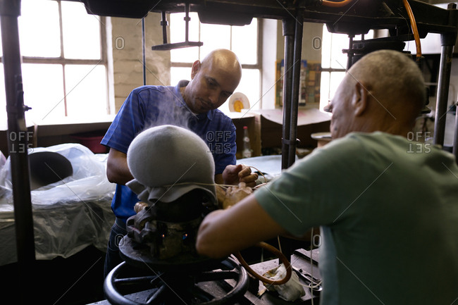 Over the shoulder view of a senior and a middle aged mixed race man working together at a machine steaming the top of a hat to shape it in the workshop at a hat factory