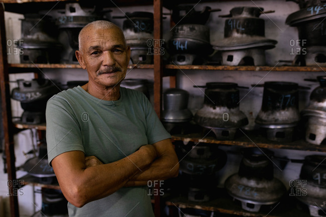 Portrait of a smiling senior mixed race man with arms crossed, standing in front of shelves of traditional equipment in the workshop at a hat factory