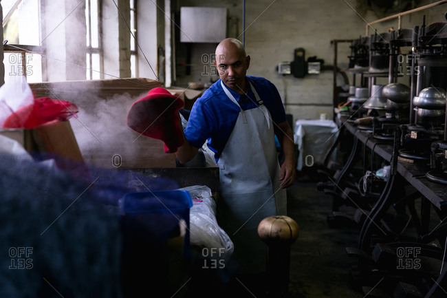 Front view of a middle aged mixed race man wearing an apron operating a piece of equipment in the workshop at a hat factory