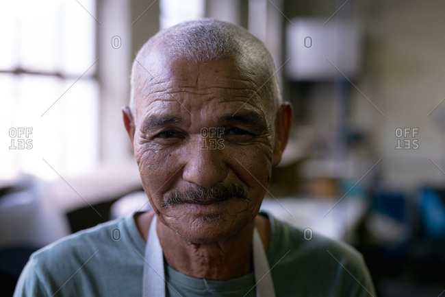 Portrait close up of a senior mixed race man looking straight to camera and smiling in the workshop at a hat factory