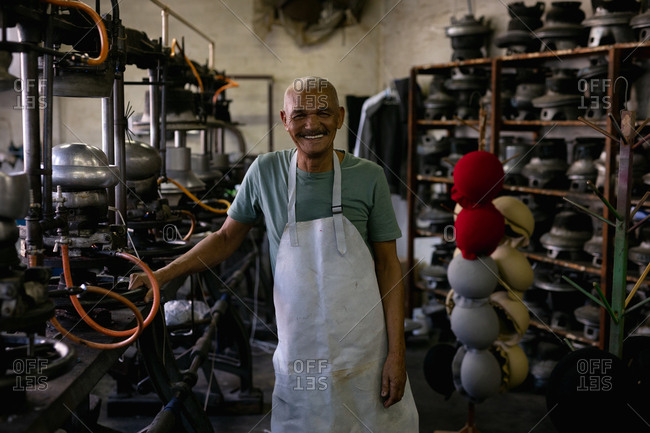 Portrait of a smiling senior mixed race man standing surrounded by traditional equipment and machinery in the workshop at a hat factory
