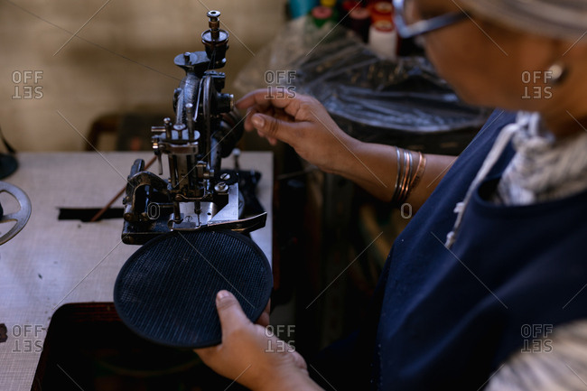 Elevated side view of a middle aged mixed race woman using a sewing machine at a hat factory