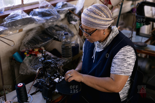 Side view close up of a middle aged mixed race woman using a sewing machine at a hat factory